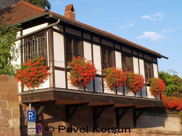 Балкон дома украшенный красными цветами.